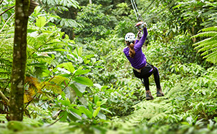 Woman zip lining through the forest