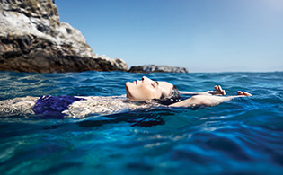 Woman floating in the ocean relaxed with her eyes closed