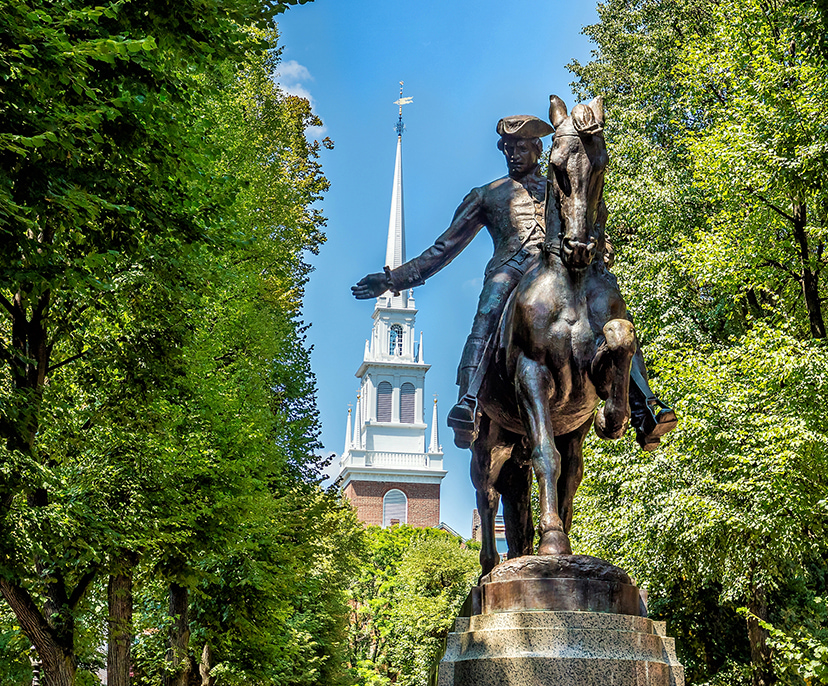 Image looking up at the Paul Revere statue surrounded by green trees and distant tall church | Click here to book now
