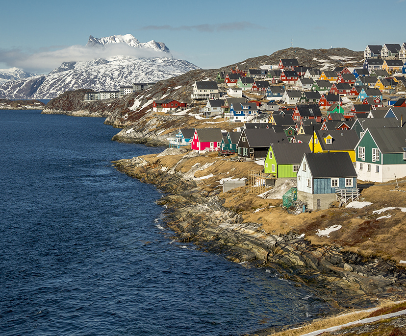 Image of a village with colorful houses by the shore and distant snowy mountains | Click here to book now