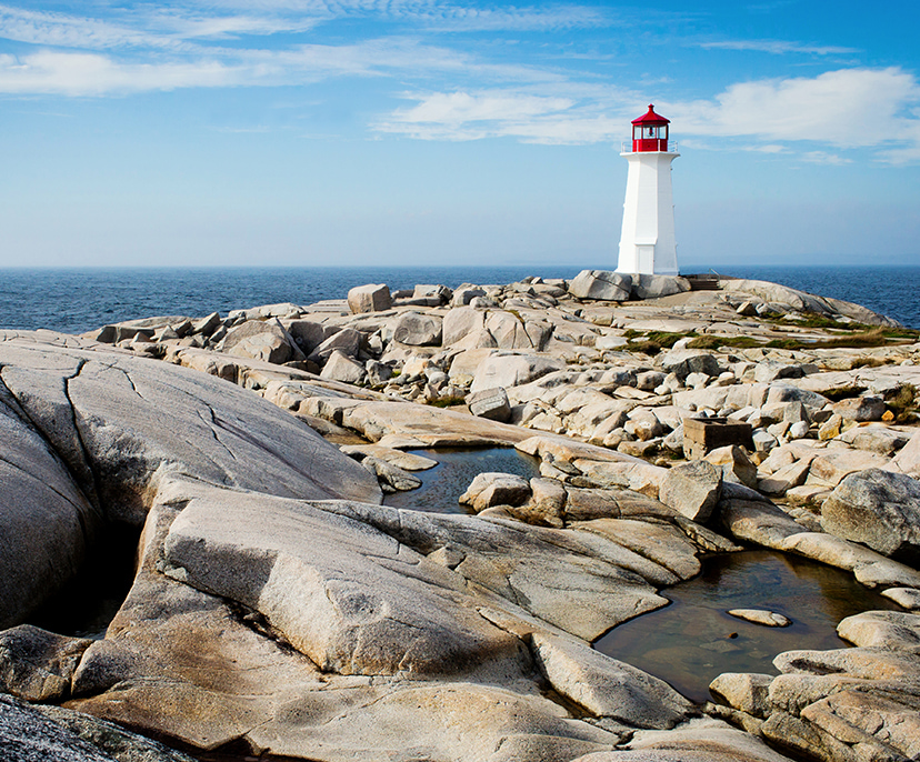 Image of a lighthouse facing an ocean and blue sky and rocks in the foreground | Click here to book now