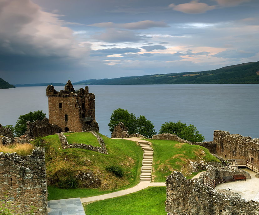 Image of a ruined castle on top a hill with a lake in the distance | Click here to book now
