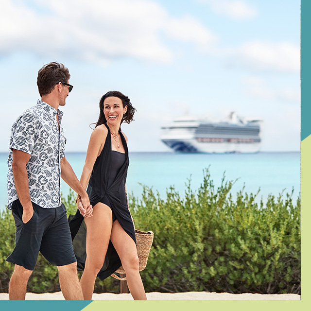 A man and woman walking next to the beach with crise ship in the background
