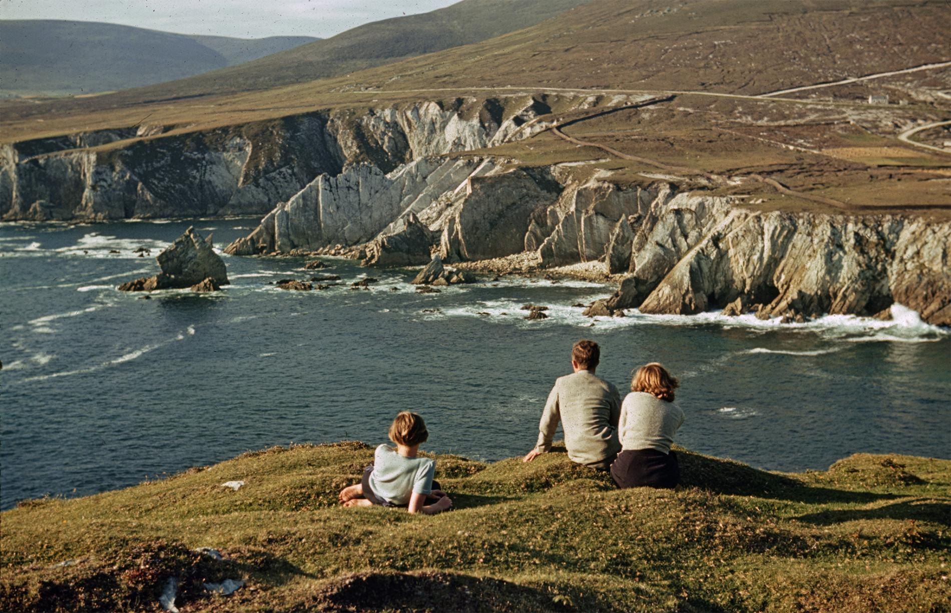 People relax by Ashleam Bay on Ireland's Achill Island in a photo from a 1940 National Geographic. In the distance, a low wall keeps cattle and sheep from falling off the cliffs.